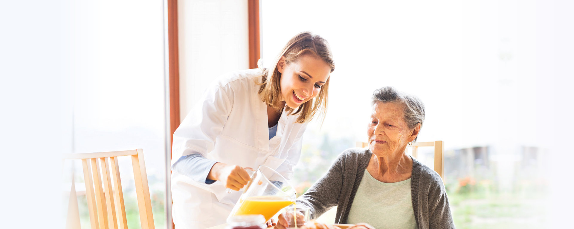 caregiver serving juice to an elderly woman
