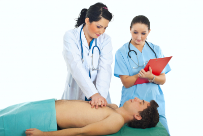 Doctor training a student to do cardiopulmonary resuscitation on male patient