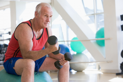 elderly man Using Hand Weights On Swiss Ball At Gym